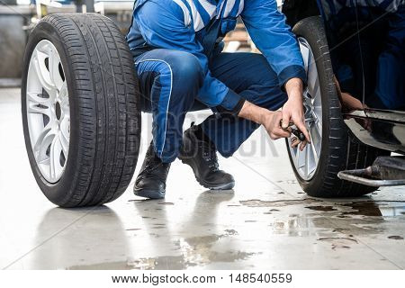 Low section of male mechanic crouching while changing car tire at garage