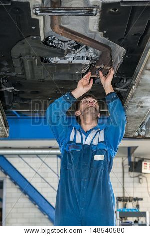 Low angle view of young male mechanic examining exhaust system of car at garage