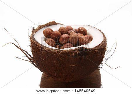 hazelnuts in a split coconut on white background