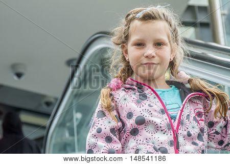 child girl on moving escalator