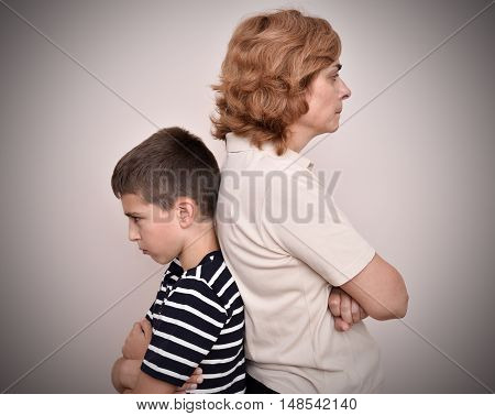 Angry mother and son turning their backs to each other