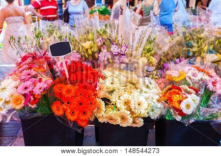 Vases of flowers on the market in Nice. A small shop with fresh flowers and bouquets of flowers. Armful of bright colored gerbera.