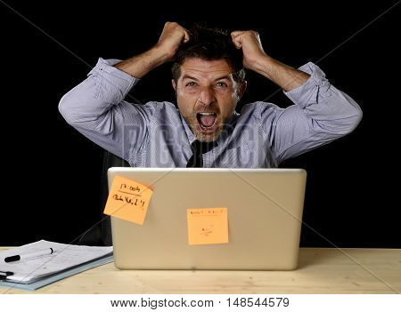 young crazy stressed businessman screaming desperate pulling hair in stress with laptop computer heavy work load isolated on office desk black background in overwork overtime concept