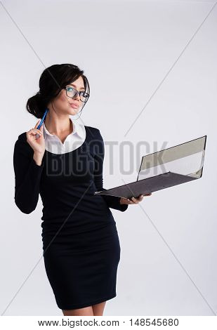 Young Caucasian woman wearing a dark blue dresst and and a white shirt, holding a ring binder folder and pen. Isolated on light background