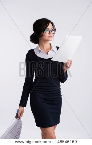 Thoughtful woman with clipboard standing isolated on a white background.