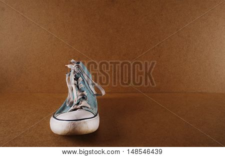 one blue sneaker on a wooden background