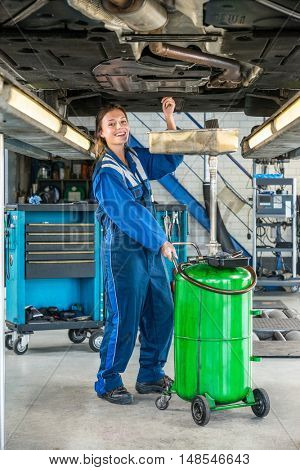 Full length portrait of smiling female mechanic repairing car on hydraulic lift in garage