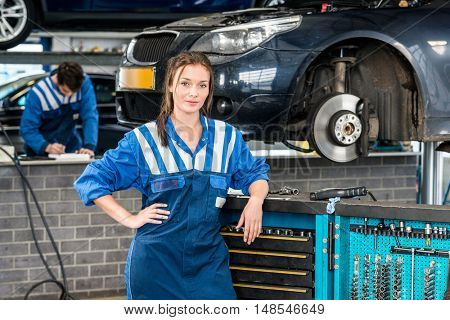 Portrait of young female mechanic standing by tool trolley with colleague in background at garage