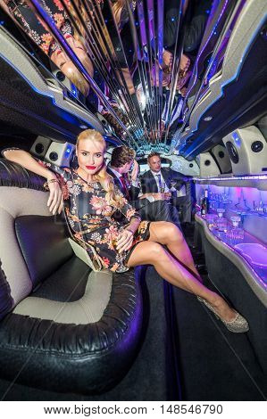 Beautiful Young Woman Holding Champagne Flute In Limousine