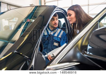 Young male mechanic sitting in car while explaining to female client at garage