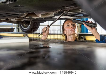 Young female mechanic with flashlight repairing car on hydraulic lift in automobile shop