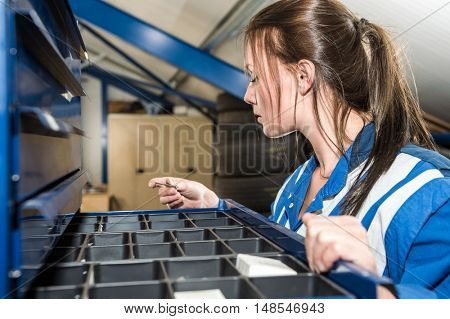 Young female mechanic selecting screw from drawer in warehouse at garage