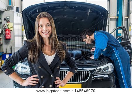 Portrait of smiling young businesswoman with mechanic repairing car in background at garage