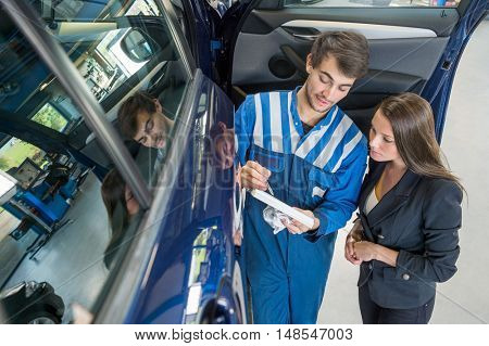 Male mechanic with female customer going through maintenance checklist by car in garage