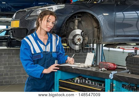 Portrait of confident young female mechanic writing notes with cars in background at garage