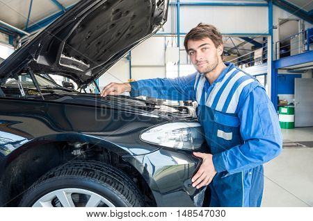 Portrait of young male mechanic repairing car engine in garage
