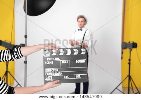 Movie clapper and young man on background in photo studio