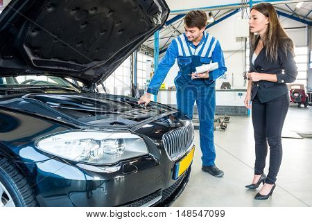 Young male mechanic talking to female customer about car engine in garage