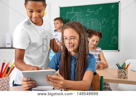Pupils with tablet computer in classroom