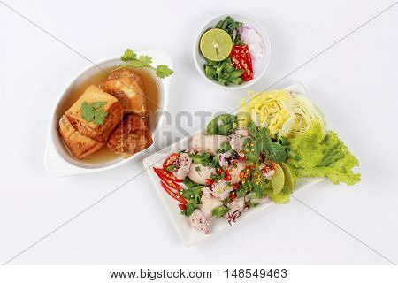 Gold bar soup as fried tofu wrap minced pork in soup served with spicy and sour mixed herb salad with squid wrap minced pork . Top view.