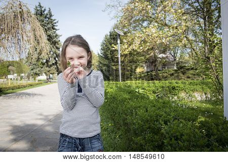 Little cute blonde girl having fun and enjoying a beautiful day in a park