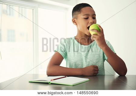 African American boy eating apple on light background