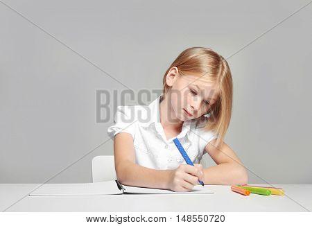 Cute girl making homework at home