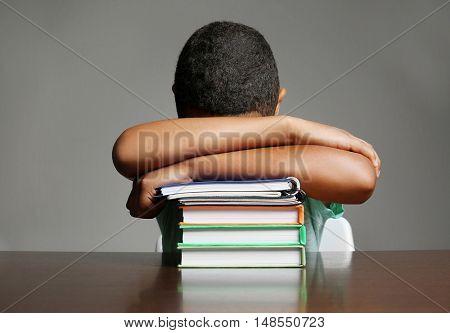 African American boy sleeping on books on grey background