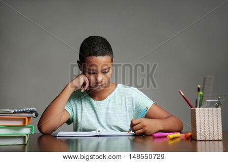 African American boy making homework on grey background