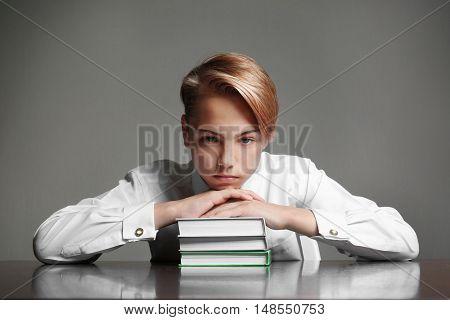 Tired boy lying on books on grey background