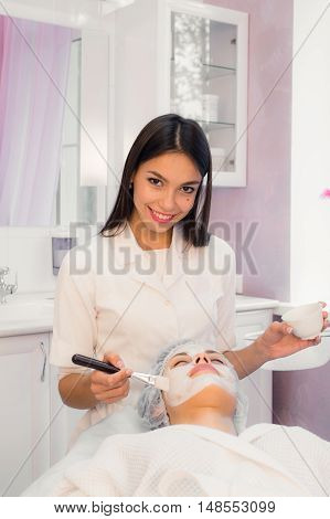 Cheerful young cosmetologist is massaging female face with a roller. She is standing and smiling. The woman is lying with pleasure.