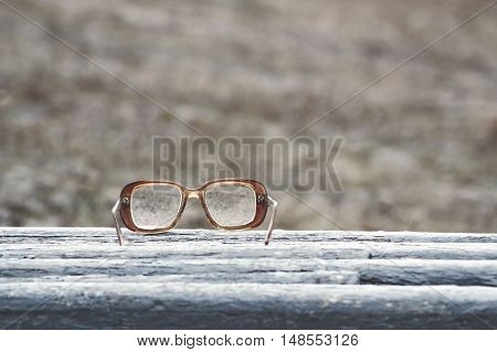 Old glasses on a park bench or table with natural background toned with a retro vintage filter app or action effect.