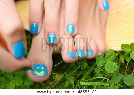 bare feet and hands with creative teens manicure and pedicure on the green grass lawn background