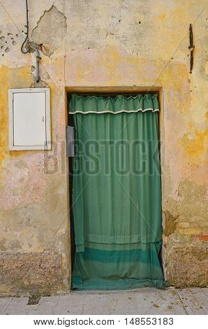 An old door covered by a green cloth in Marano Lagunare in Friuli Venezia Giulia north east Italy.