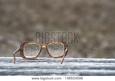 Vintage glasses on a park bench or table with natural background toned with a retro vintage filter app or action effect.