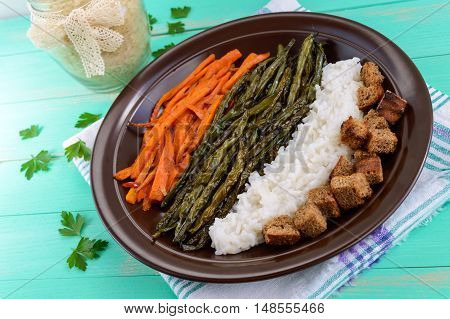 Baked vegetables (asparagus beans and carrot) boiled rice and rye croutons. Vegetarian cuisine. Close up