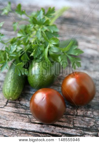 Fresh different vegetables - tomatoes and cucumber on wooden background