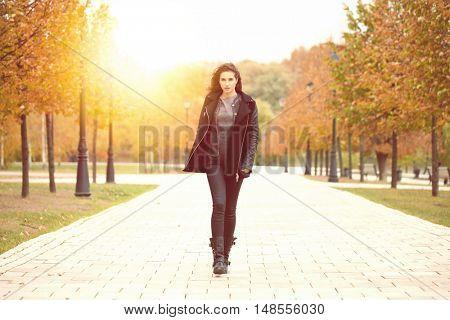Beautiful woman in black coat walking autumn street
