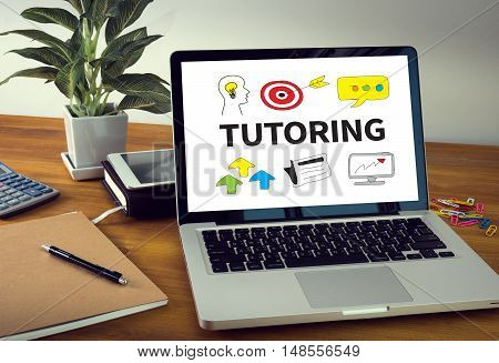 TUTORING Laptop on table. Warm tone businessman working