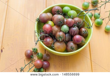 Top view of cherry tomatoes in bowl on wooden background.