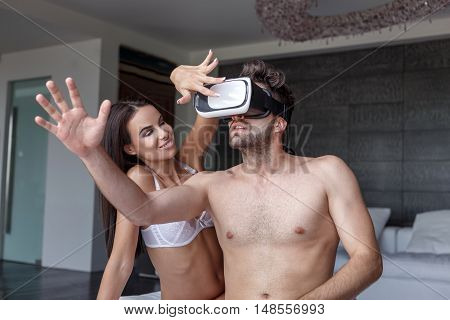 Sexy young couple playing on VR glass headset indoor virtual reality