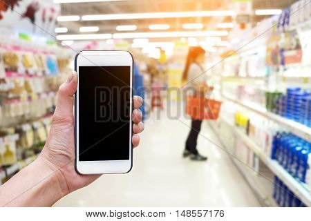 Human Holding Smart phone showing blank screen in blurred supermarket