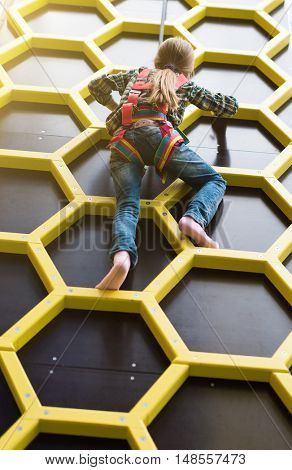 little girl climbing the wall on safety ropes barefoot in entertainment center