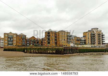 High-rise Riverside red brick houses on the Thames river in London Borough of Tower Hamlets London England.