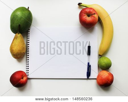 Note book paper with blank empty page and colorful organic fresh fruits apple banana pear peach mango isolated on white table background Diet fitness planning, healthy eating food nutrition lifestyle concept with copy space