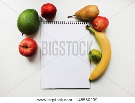 Notebook planner with blank empty page and colorful organic fresh fruits apple banana pear peach mango isolated on white table background Diet fitness planning, healthy eating food weight loss nutrition lifestyle concept with copy space close up