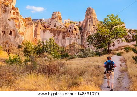 Tourist walking along cave rocks in Cappadocia, a historical region in Central Anatolia, Turkey
