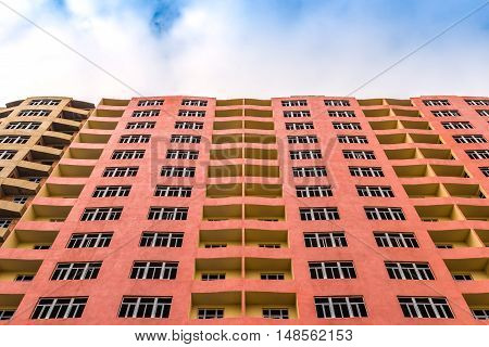 High multistory building. Tall apartment building with balconies