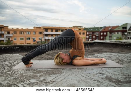 Beautiful woman practicing yoga on the roof,Halasana/Plow pose