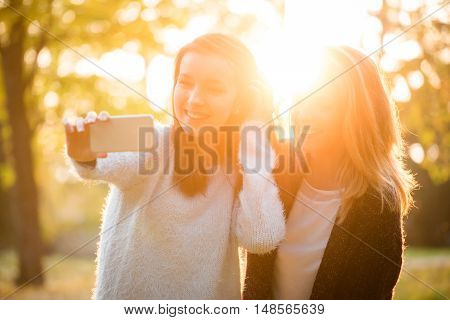 Friends - two teenage girls taking selfie with smartphone in nature at sunset time